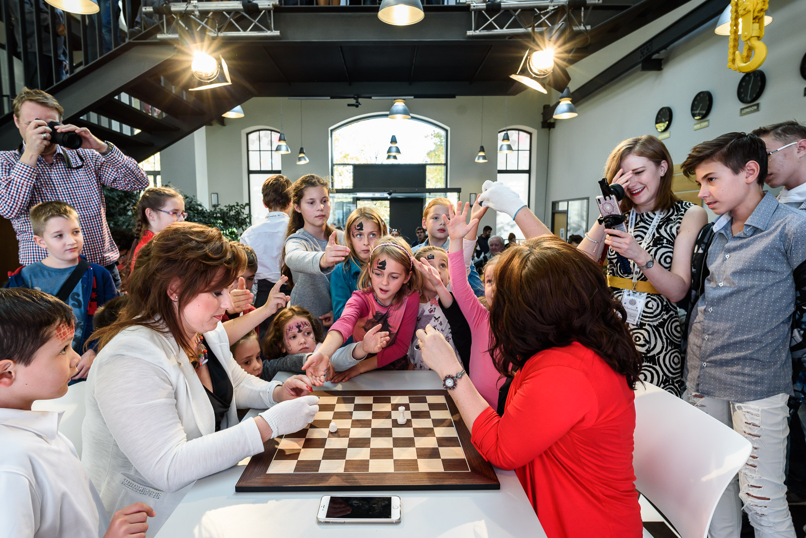 Judit and Sofia give away marzipan chess pieces to children